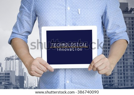 young man showing digital tablet with TECHNOLOGICAL INNOVATION in city  , business concept ,business idea , strategy concept - stock photo