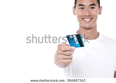 Young man showing his debit card over white