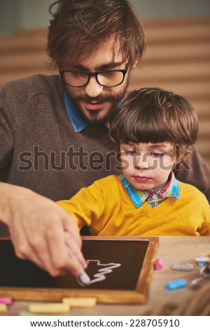 Young man showing his son how to draw on board with chalk - stock photo