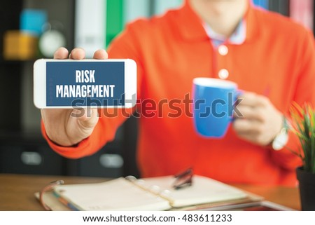 Young man showing smartphone and RISK MANAGEMENT word concept on screen