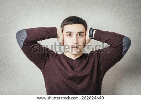 young man shows he does not want to hear . Fingers in his ears - stock photo