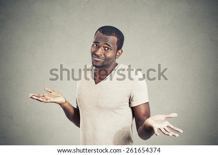 Young man shrugging shoulders who cares so what I don't know gesture isolated on grey wall background. Body language  - stock photo