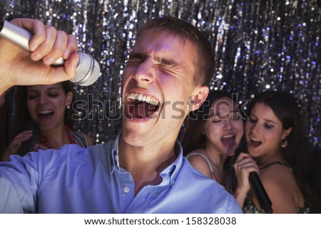 Young man singing into microphone at karaoke - stock photo