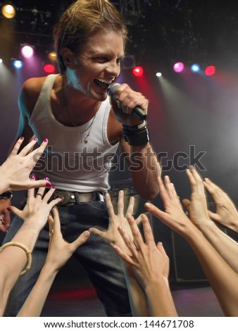 Young man singing on stage in concert close to adoring fans - stock photo
