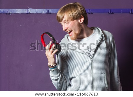 Young man singing to his headphones in cool location