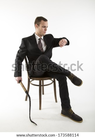 young man sits on a chair and looks at the clock with whip in hand  on white background - stock photo