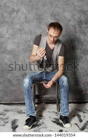 Young man sits on chair in empty room powdered with snow and intersperses snow from one hand to another - stock photo