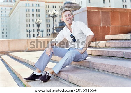 Young man sits on the steps of the architectural complex - stock photo
