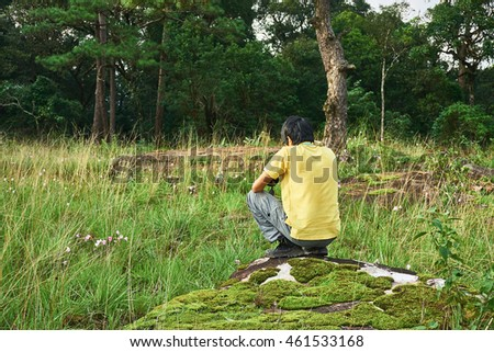 Young man sits on the stone which is situated at the grass field.