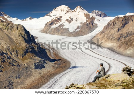 Young man sitting and enjoying a majestic view to Aletsch glacier, the largest gracier in Alps and UNESCO herritage from Eggishorn, Valais, Switzerland, Europe - stock photo