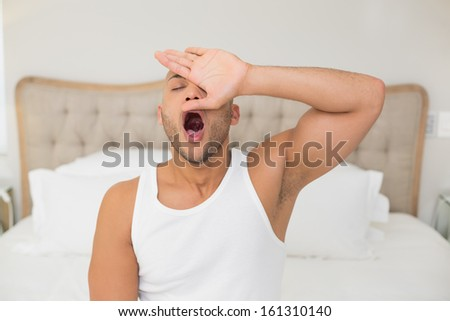 Young man sitting and yawning in bed at home