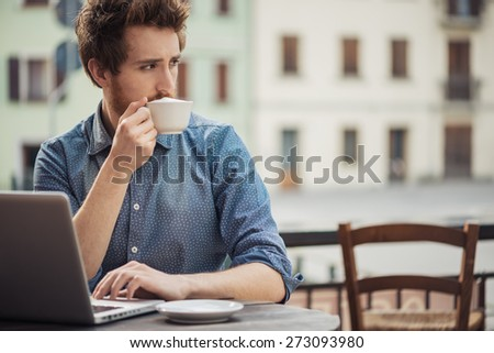 Young man sitting at bar table having a cappuccino and using a laptop, city buildings on background - stock photo