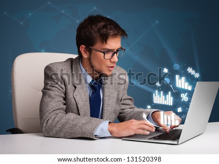 Young man sitting at desk and typing on laptop with diagrams and graphs comming out - stock photo