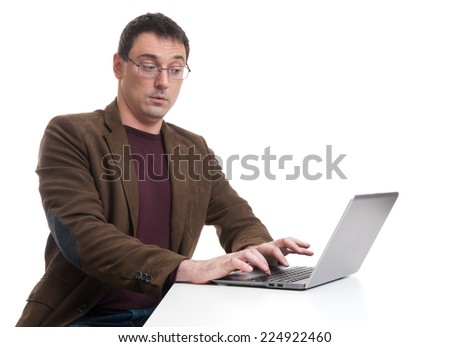 young man sitting at desk and working on laptop computer