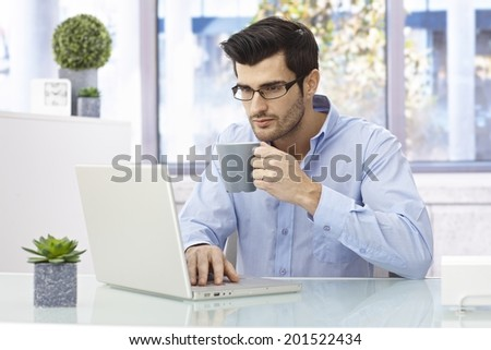 Young man sitting at desk at home, working on laptop computer, drinking coffee. - stock photo