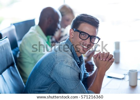 Young man sitting at his desk smiling at camera while colleagues sitting in the background