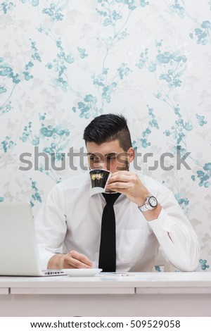 Young man sitting at table using laptop and drinking coffee