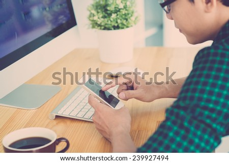 Young man sitting at the table and using smartphone - stock photo