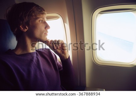 young man sitting at the window of the plane. traveler in the airplane - stock photo