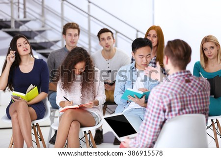 Young man sitting back in front of people at the office meeting