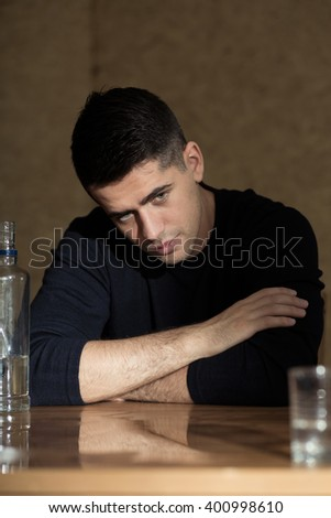 Young man sitting beside table, bottle of vodka and glass next to him - stock photo