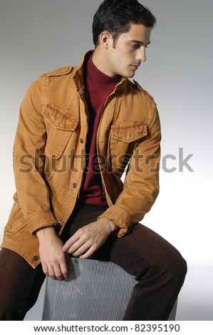 young man sitting cube against shot in studio - stock photo