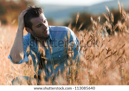 Young man sitting in a field - stock photo