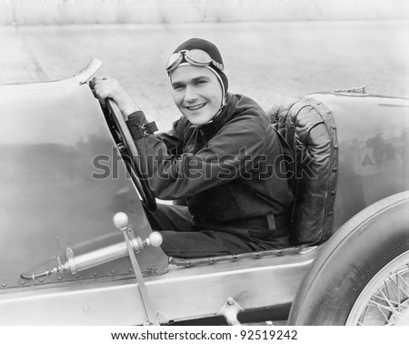 Young man sitting in a race car with a big smile - stock photo