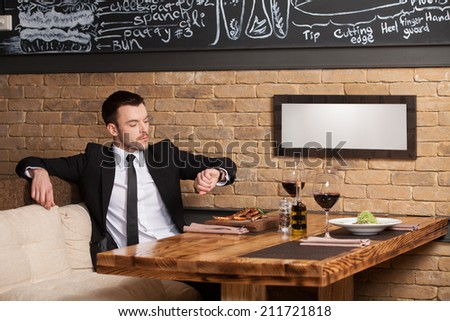 young man sitting in cafe waiting for somebody. handsome guy looking at his handwatches and waiting for girl - stock photo