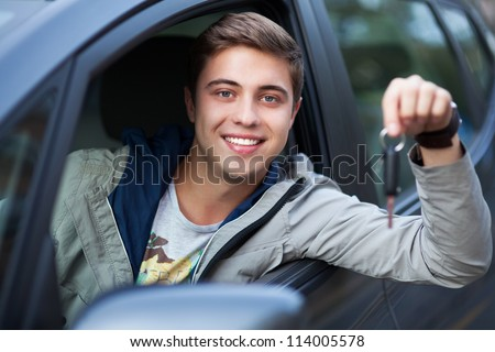 Young man sitting in car holding car keys - stock photo
