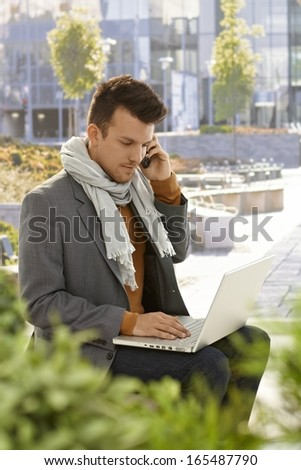 Young man sitting in citypark, using laptop computer, talking on mobilephone. - stock photo