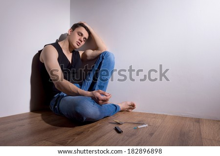 young man sitting in corner with needle. handsome guy in jeans closed eyes