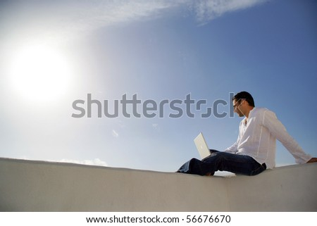 Young man sitting in front of a laptop computer face to the sea