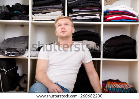 Young man sitting in front of his wardrobe.  - stock photo