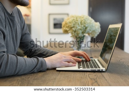 Young man sitting in front of the screen with his hands on the keyboard. Laptop on the table - stock photo