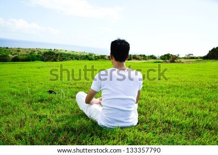 Young man sitting in lotus position out side - stock photo