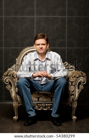 young man sitting in magnificent ancient armchair - stock photo