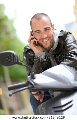 Young man sitting in motorcycle with telephone - stock photo