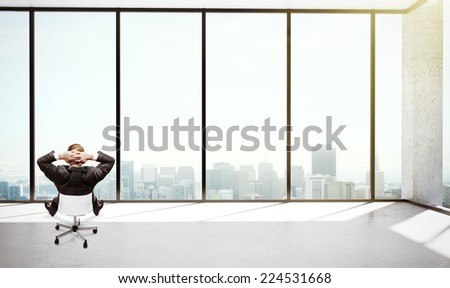 young man sitting in office and thinking - stock photo
