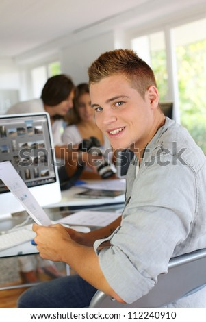 Young man sitting in office in front of desktop computer - stock photo