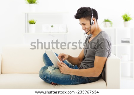 young Man sitting in sofa and using  tablet pc - stock photo