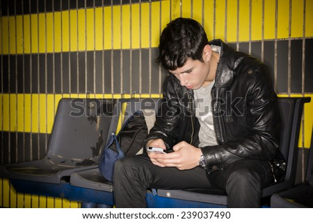 Young man sitting in station typing on smartphone waiting for subway train - stock photo