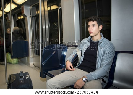 Young man sitting in subway train commuting to work looking away - stock photo