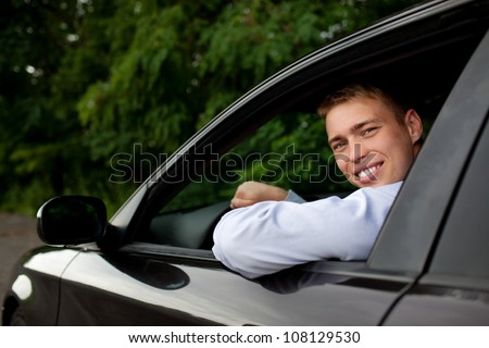 Young man sitting in the car smiling - stock photo