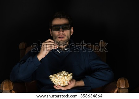 young man sitting in the dark room in the front of tv watching movie and eating popcorn, wearing 3d glasses - stock photo