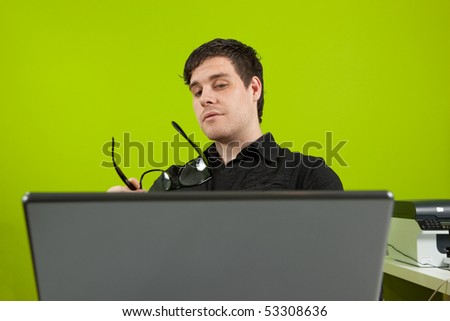 Young man sitting in the office and working on the laptop - stock photo