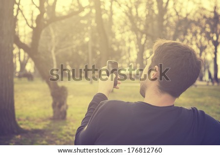 Young man sitting in the park and texting a message