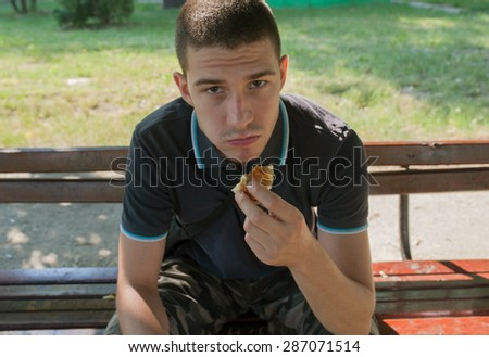 Young man sitting on a bench and eating - stock photo