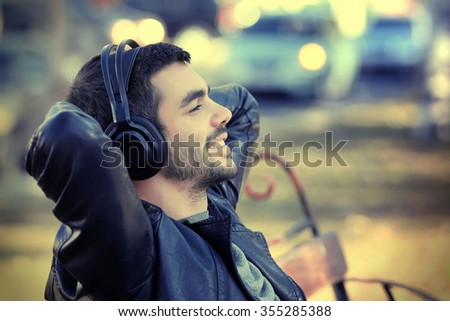 Young man sitting on a bench in park and listening to music - stock photo