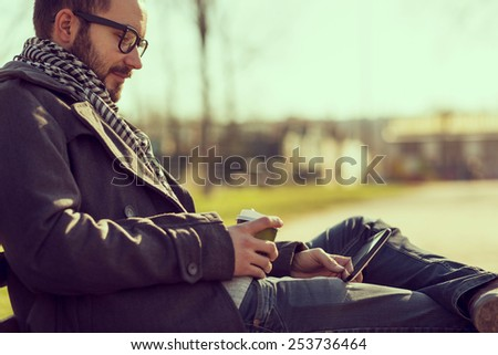 Young man sitting on a bench, reading an e-book on a tablet and drinking coffee - stock photo
